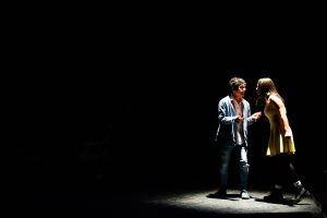 Two characters converse animatedly on stage in spotlight